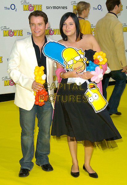 "STEPHEN GATELY & GUEST.""The Simpsons Movie"" UK premiere at the Vue O2 Arena cinema, London, England..July 25th, 2007.full length denim jean jacket masks balloons black dress white.CAP/CAN.©Can Nguyen/Capital Pictures"