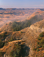 NDTR_125 - USA, North Dakota, Theodore Roosevelt National Park, Morning fog hangs above autumn colored plains and sedimentary hills, view south from Boicourt Overlook, South Unit.
