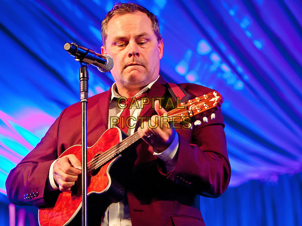 Jack Dee.Day Three of Latitude Festival, Henham Park, Southwold, Suffolk, England..July 15th 2012.on stage in concert live gig performance performing music half length  white red maroon burgundy suit shirt guitar.CAP/PP/MM.©Mike Mustard/PP/Capital Pictures.