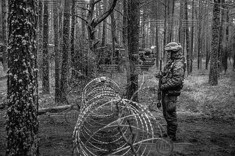 A Lithuanian soldier on guard at the entrance to the command advanced position during NATO Iron Sword joint exercises.