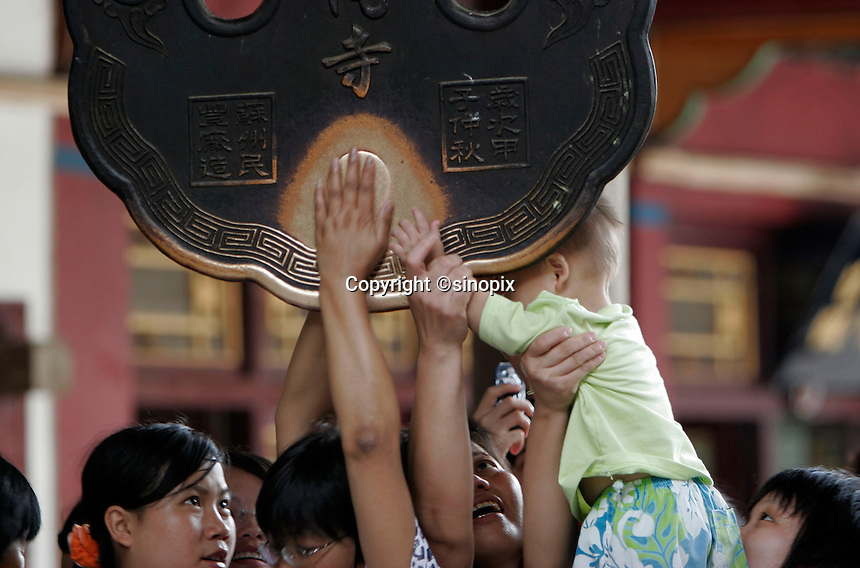 With help from adults, a child rubs a hanging bronze plate for luck at the Nanputuo Buddhist Temple in Xiamen, China..06 Oct 2005