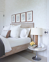 The guest bedroom's bed and rug are by Serena & Lily. A lamp and other items stand on the pedestal bedside table.