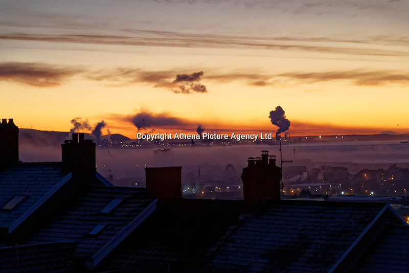 Smoke from Port Talbot Steel Works is visible in the horizon, seen over roof tops during an early frosty morning in Swansea, Wales, UK. Tuesday 12 December 2017