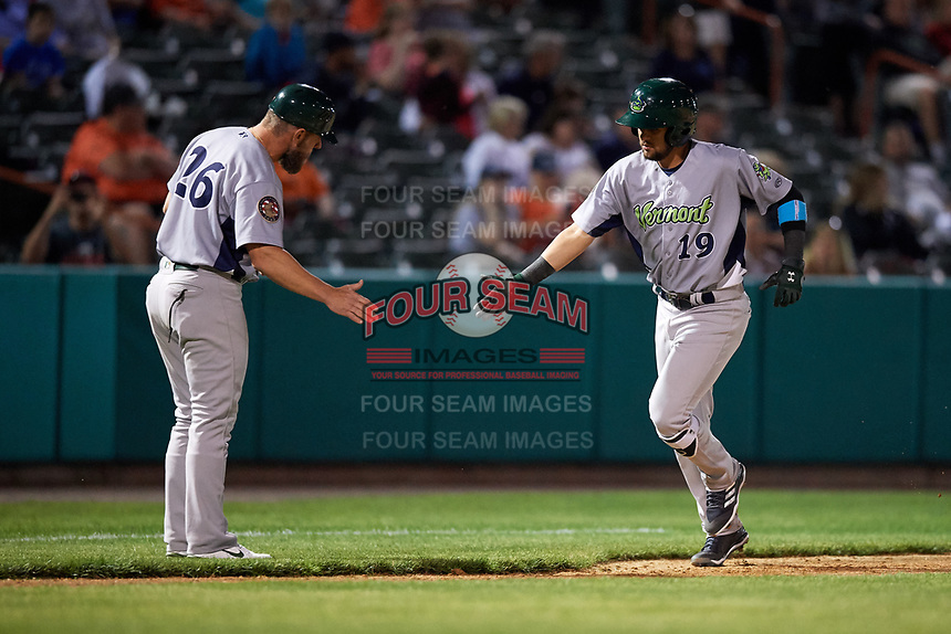 Vermont Lake Monsters third baseman Javier Godard (19) is congratulated by manager Aaron Nieckula (26) as he rounds third base after hitting a home run in the top of the ninth inning during a game against the Tri-City ValleyCats on June 16, 2018 at Joseph L. Bruno Stadium in Troy, New York.  Vermont defeated Tri-City 6-2.  (Mike Janes/Four Seam Images)