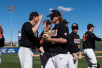 Oregon State Beavers starting pitcher Bryce Fehmel (26) is high-fived by teammates between innings of a game against the Gonzaga Bulldogs on February 16, 2019 at Surprise Stadium in Surprise, Arizona. Oregon State defeated Gonzaga 9-3. (Zachary Lucy/Four Seam Images)