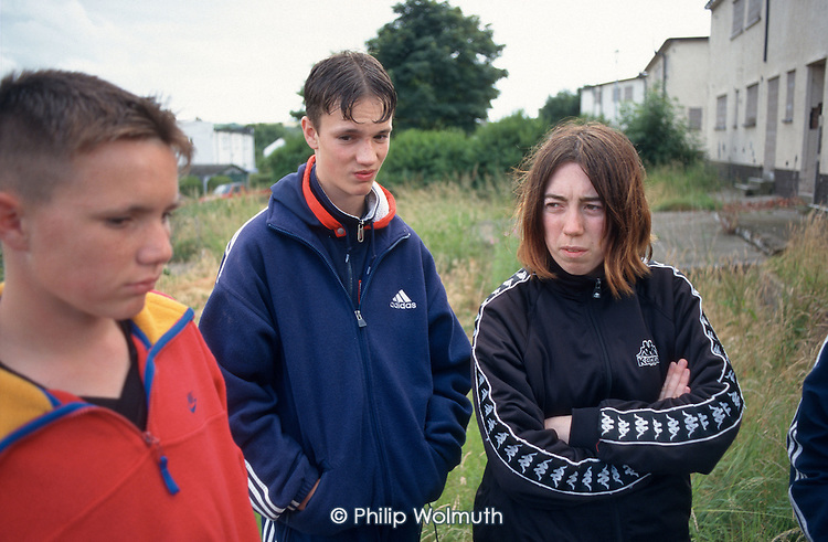 "Teenagers pass the time outside boarded up and empty houses on an estate in Distington, Cumbria, which suffers from ""low demand"" as a result of high local unemployment."