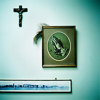 A crucifix, an old panoramic photograph of Macau and an embroidered image of hands clasped in prayer adorn a wall in the office of 85 year old missionary Father Lancelot...