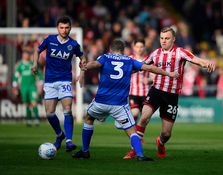 Lincoln City's Harry Anderson vies for possession with Macclesfield Town's David Fitzpatrick<br /> <br /> Photographer Chris Vaughan/CameraSport<br /> <br /> The EFL Sky Bet League Two - Lincoln City v Macclesfield Town - Saturday 30th March 2019 - Sincil Bank - Lincoln<br /> <br /> World Copyright © 2019 CameraSport. All rights reserved. 43 Linden Ave. Countesthorpe. Leicester. England. LE8 5PG - Tel: +44 (0) 116 277 4147 - admin@camerasport.com - www.camerasport.com