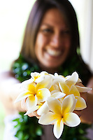 A beautiful young Hawaiian woman holding fragrant plumerias in her hands