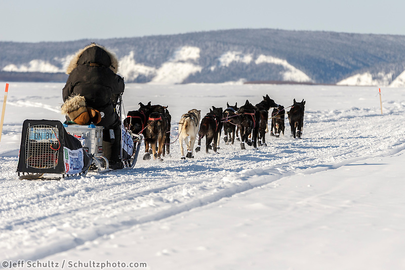 Lance Mackey's license plate &quot;ON BY&quot; shows on his dog carrier as he runs down the Yukon River after leaving the Koyukuk checkpoint on the afternoon of Sunday  March 15, 2015 during Iditarod 2015.  <br /> <br /> (C) Jeff Schultz/SchultzPhoto.com - ALL RIGHTS RESERVED<br />  DUPLICATION  PROHIBITED  WITHOUT  PERMISSION