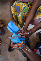 Africa, DRC, Democratic Republic of the Congo, South Kivu, Kamanyola. Women for Women project. WFW Kamanyola co-op and lifeskills training. Women making medicinal soap to sell.  Kiza Mugala carving the soap.