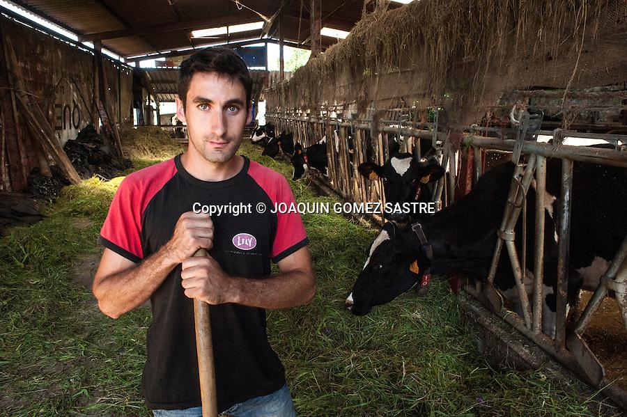 El ganadero David posa con sus vacas en la explotacion gamnadera de su propiedad en Miengo  (Cantabria)