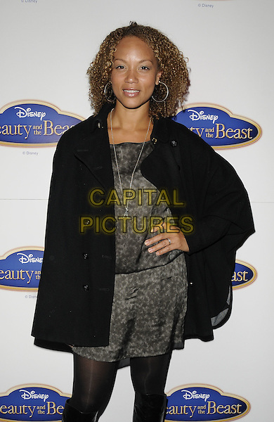 "ANGELA GRIFFIN .At Disney's ""Beauty And The Beast"" gala screening, Cafe de Paris, London, England, UK, September 26th 2010..half length black coat cape hand on hip grey gray print dress  tights .CAP/CAN.©Can Nguyen/Capital Pictures."