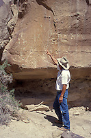 Ute Indian guide pointing at anciebt Anasazi petrolyphs, Ute Mountain Tribal Park, Colorado, U.S.A.