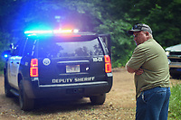 NWA Democrat-Gazette/CHARLIE KAIJO Bill Cowger of Gravette looks on as a Benton County Sheriff's Deputy vehicle blocks the intersection of Crossover Rd and Gorden Hollow Rd, Friday, July 5, 2019 in Gravette. <br /> <br /> Police responded to a shooting situation that left four people dead in an apparent murder suicide on a nearby property. All four people are related or lived at the residence. One body was found on the driveway. Authorities do not believe there is a danger to the public.