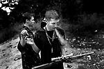 Brothers share a smoke at a gun range, Swisher, 2002