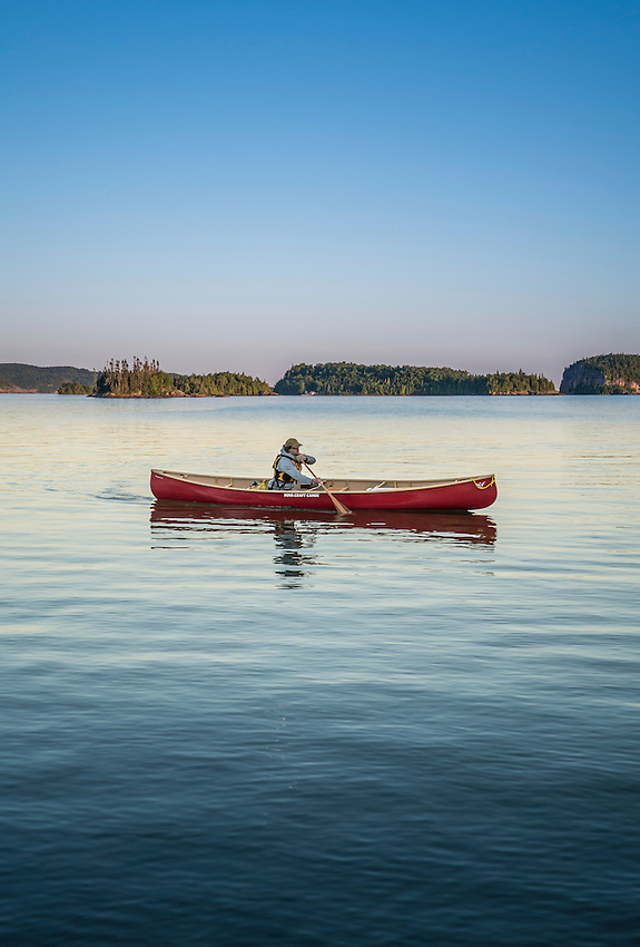 Solo canoeist at dusk on Lake Superior at Lake Superior Provincial Park, Ontario, Canada.