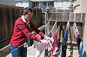 A woman (30-40 years) hanging laundry in her backyard and therefore saving both money and energy. Milbrae, California, USA