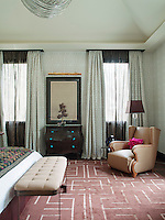 In one of the bedrooms, floor to ceiling windows are dressed with Dedar fabric curtains which match the wallpaper