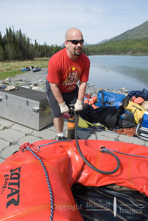 Nick Lynch pumps up a raft at Cooper Landing, along the Kenai River in Alaska.