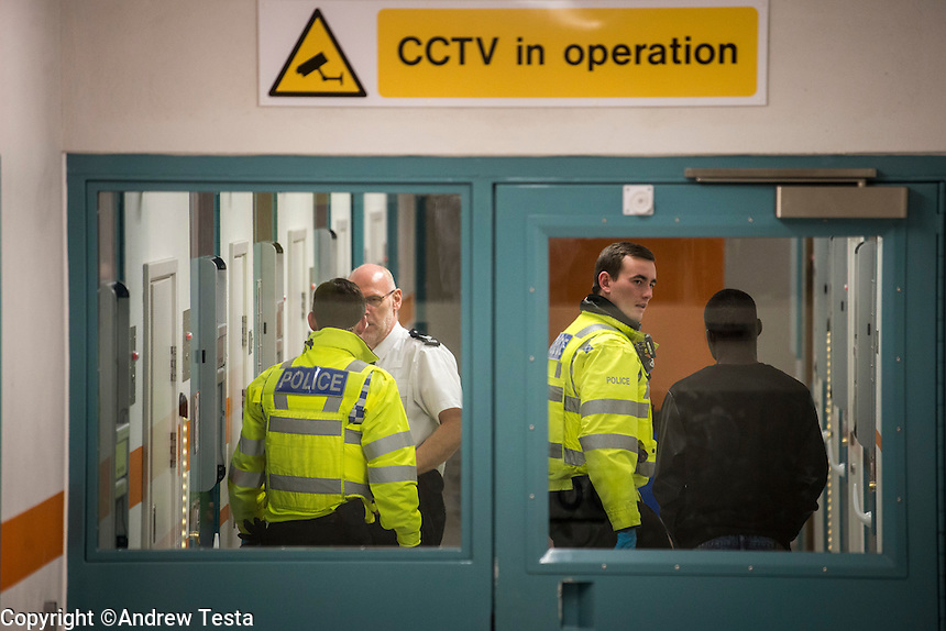 UK. Northampton. 7th December 2013<br /> A man arrested for being drunk and disorderly is taken to  the cells in northampton.<br /> &copy;Andrew Testa for the New York Times