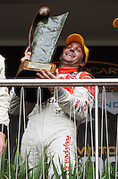 Jamie Whincup struggles with the weight of the Mark Porter Trophy after winning both races of the weekend during Day Three of the Hamilton 400 Aussie V8 Supercars Round Two at Frankton, Hamilton, New Zealand on Sunday, 19 April 2009. Photo: Dave Lintott / lintottphoto.co.nz
