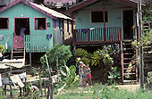 Manaus, Brazil. Boy taking a bath using a tin can outside his timber stilt house in bright sunshine.