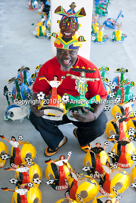 JOHANNESBURG, SOUTH AFRICA - MAY 10: Alfred Baloyi, an artist, shows some of his newly designed Makarapa Helmets in his new studio in Wynberg, north of Johannesburg, South Africa. Mr. Baloyi, and a diehard Kaizer Chiefs soccer fan, started to make these hats in 1979. Initially he asked a friend who worked at a construction site for a helmet, as he wanted to protect himself from missiles at games. He later started to paint it, and later started to make this different figures hand cut out from the helmet. During the years he has made many different artistic hats that are on display in his studio in a shack in Primrose, Johannesburg. He later gave up his job as a washer of busses. From his small workshop in a squatter camp in Primrose south east of Johannesburg he recently made partner with an investor and have a brand new factory with about fifty people employed to make the hats. (Photo by Per-Anders Pettersson/Getty Images)
