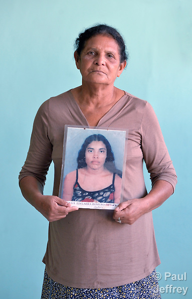 Dilma Pilar Escobar Medina holds a photo of her daughter Olga Romero Medina in El Progreso, Honduras. The young woman left for the United States in 2009, but her mother hasn't heard from her since a few months later when she phoned from southern Mexico. Escobar Medina cares for five children that her daughter left behind, and is a member of a group of mothers of migrants who have disappeared on their journey north.