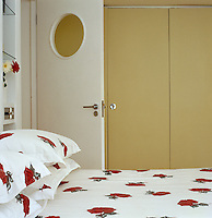 Simple fitted wardrobes line the walls of this small bedroom