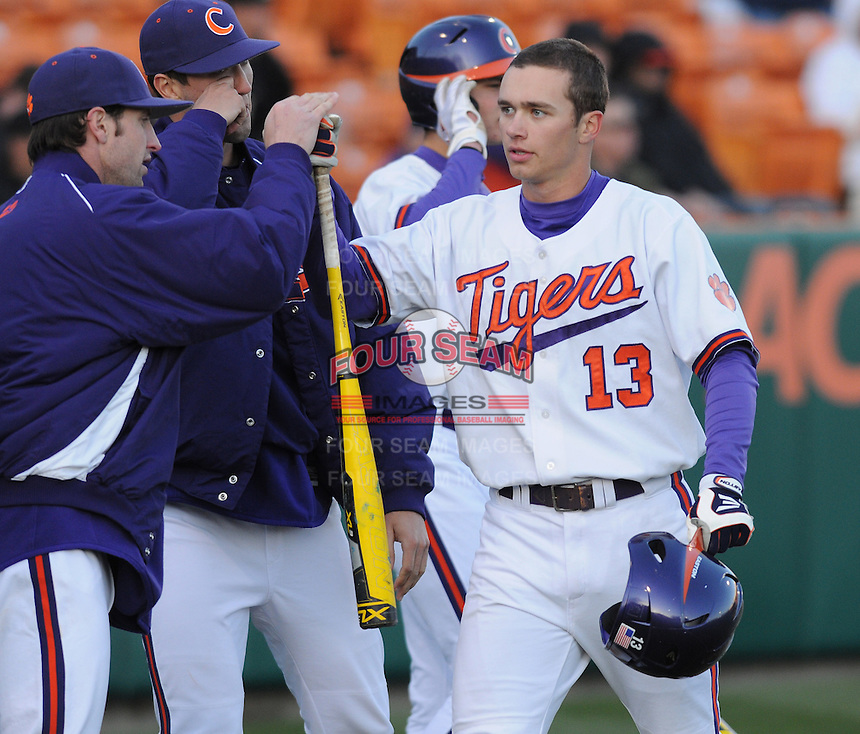 Jay Baum (13) of the Clemson Tigers is congratulated after scoring a run in the seventh inning of a game against the Wofford Terriers on Wednesday, March 6, 2013, at Doug Kingsmore Stadium in Clemson, South Carolina. Clemson won, 9-2. (Tom Priddy/Four Seam Images)