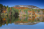 Whitesides mountain and fall foliage are reflected in a small lake.
