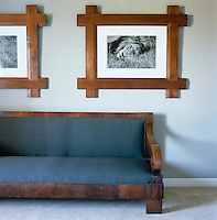Black and white photographs of African wildlife are displayed in Arts and Crafts oak frames above a 19th century Italian walnut bench