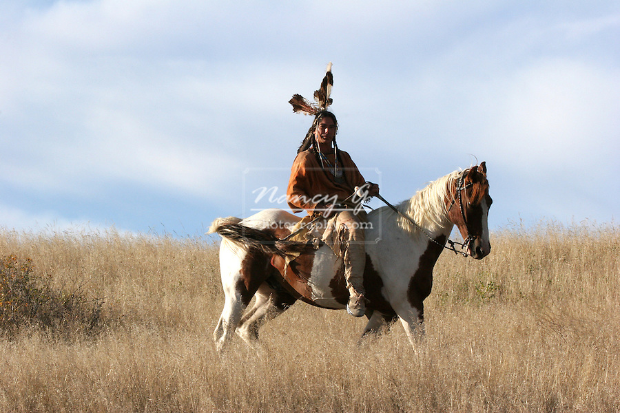 A Native American Indian man on horseback riding the ...