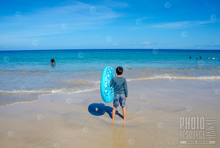 Boy with blue inner tube standing at the shoreline of Hapuna Beach, along the Kohala Coast of the Big Island. This white sand beach has been rated one of the best beaches in the world.