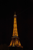 The Eiffel Tower glows in the darkness of Paris