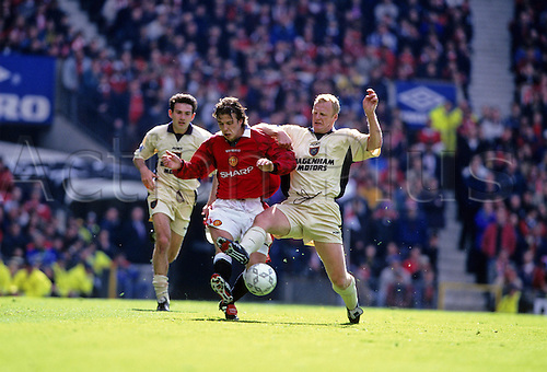 11 May 1997: Manchester United midfielder David Beckham is tackled by Iain Dowie during the Premier League match between Manchester United and West Ham at Old Trafford. Manchester United won the match 2-0. Photo: Glyn Kirk/Actionplus..970823 man men football footballer player tackle tackling challenge