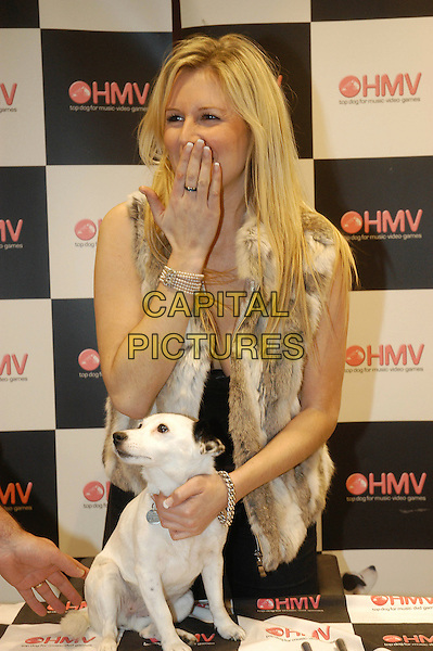 ABI TITMUSS.Opening HMV in Chelmsford.December 2nd, 2004.half length, fur vest, dog, animal pet, covering mouth, gesture.www.capitalpictures.com.sales@capitalpictures.com.©Capital Pictures