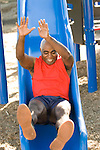 Man on playground slide
