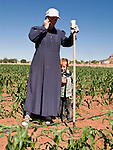 """June 16, 2008 -- COLORADO CITY, AZ: A member of the Jessop family makes a cell phone call while weeding the community corn plot in Colorado City, AZ. The Jessops are a polygamous family and members of the FLDS. Colorado City and neighboring town of Hildale, UT, are home to the Fundamentalist Church of Jesus Christ of Latter Day Saints (FLDS) which split from the mainstream Church of Jesus Christ of Latter Day Saints (Mormons) after the Mormons banned plural marriage (polygamy) in 1890 so that Utah could gain statehood into the United States. The FLDS Prophet (leader), Warren Jeffs, has been convicted in Utah of """"rape as an accomplice"""" for arranging the marriage of teenage girl to her cousin and is currently on trial for similar, those less serious, charges in Arizona. After Texas child protection authorities raided the Yearning for Zion Ranch, (the FLDS compound in Eldorado, TX) many members of the FLDS community in Colorado City/Hildale fear either Arizona or Utah authorities could raid their homes in the same way. Older members of the community still remember the Short Creek Raid of 1953 when Arizona authorities using National Guard troops, raided the community, arresting the men and placing women and children in """"protective"""" custody. After two years in foster care, the women and children returned to their homes. After the raid, the FLDS Church eliminated any connection to the """"Short Creek raid"""" by renaming their town Colorado City in Arizona and Hildale in Utah. The Jessops are a polygamous family and members of the FLDS.     Photo by Jack Kurtz"""