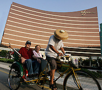 American tourists take a rickshaw ride past the Wynn Casino in Macau, Macau.