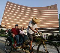 American tourists take a rickshaw ride past the Wynn Casino in Macau, Macau.