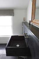 This contemporary bathroom features a smooth rectangular wash basin made from local Cornish slate