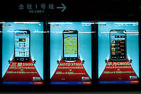 Underground landscape view of back lit retail smart phone marketing signage at a B?ij?ng dìti?zhàn in D?ngchéng Q? in Beijing.  © LAN