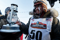 Marcelle Fressineau extinguishes the widow's lamp signifying the last musher is off the trail shorlty after she came in last and 49th place into Nome on Saturday March 15 during the 2014 Iditarod Sled Dog Race.<br /> <br /> PHOTO (c) BY JEFF SCHULTZ/IditarodPhotos.com -- REPRODUCTION PROHIBITED WITHOUT PERMISSION