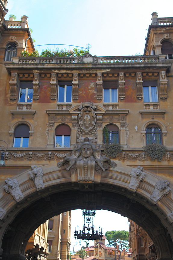 Just behind piazza Buenos Aires in Rome, the typical building made in the form of an arc, with its windows, which delimitates the typical quarter designed by Gino Coppedé. There is an old chandelier and other typical buildings of the quarter are visible on the background. Digitally Improved Photo.