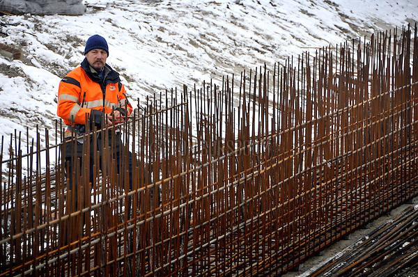 ALPHEN A/D RIJN - In Alphen a/d Rijn werkt een medewerker van Bezemer Betonstaal aan de funderingen van een havenkraan voor de nieuwe Overslag Terminal Alphen(OTA). De door  de Van Uden Group te realiseren containerhaven langs de Gouwe, is onderdeel van het nieuwbouwproject Steekterpoort waarbij tevens de N207 wordt verlegd en een duurzaam bedrijventerrein wordt aangelegd. Het terrein dat ligt ingeklemd tussen de spoorlijn Leiden - Bodegraven, de rijksweg N11, de provinciale weg N207 en de Gouwe moet volgens initiatiefnemer de gemeente Alphen a/d Rijn de komende jaren 'de spil van de economische ontwikkeling van Alphen aan den Rijn en de regio' worden. Vanwege het ontbreken van enige wind hebben de ijzervlechters het ondanks de vorst niet te koud om hun handschoenen uit te laten tijdens het vlechten van de stalen staven. COPYRIGHT TON BORSBOOM