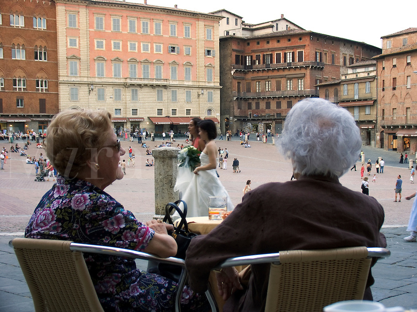 Two women at cafe table on the Piazza Del Campo sit in front row seats watching the world pass before them, Siena, Ital
