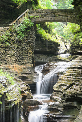 Bridge over waterfall in scenic Watkins Glen Gorge, stone, rock, and water, a state park in New York, NY, USA.