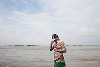 A man takes his bath in the River Padma.Every year in Bangladesh, millions of people are affected by river erosion that destroys home, farmland, communication infrastructure. In the last couple of days erosion by the Padma River has caused extensive damages to houses, agricultural lands, roads etc. In Dohar, lots of people lost their lands and homes due to Padma river banks erosion. Dohar, Dhaka, Bangladesh.